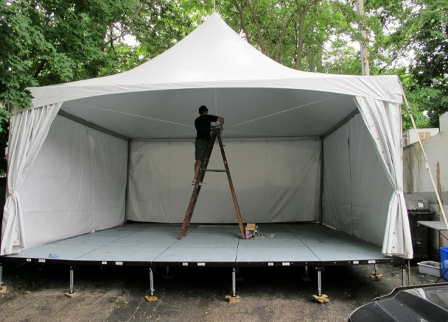 20X20 HIGH PEAK TENT WITH SIDE CURTAINS OVER STAGE